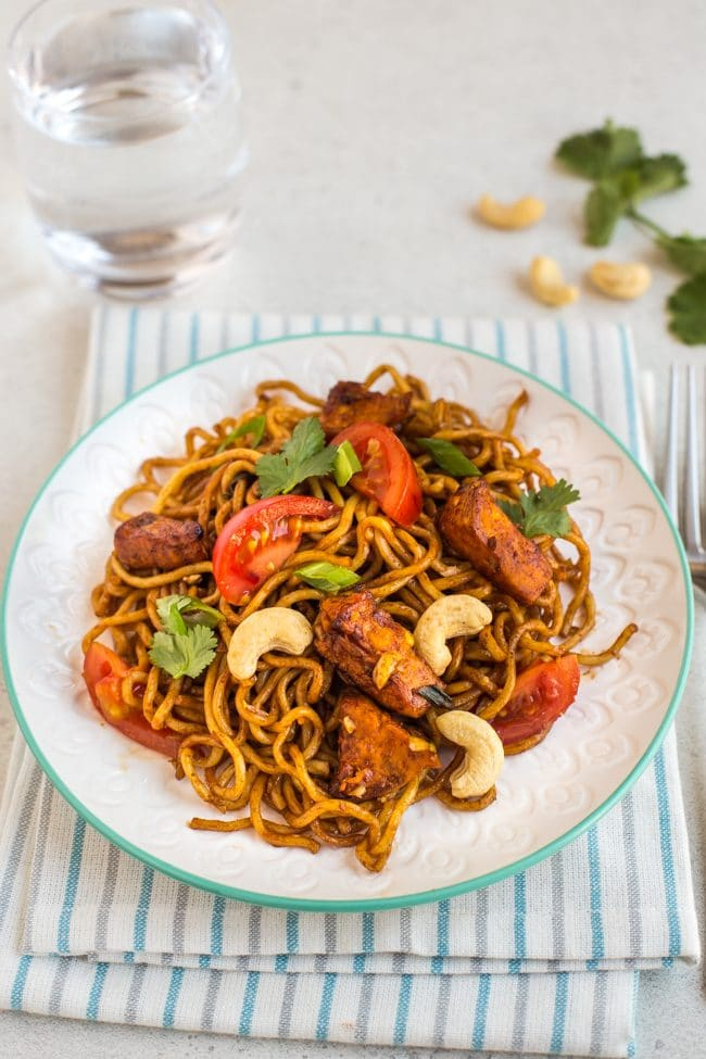Spicy sweet potato noodles with tomatoes and cashew nuts on a plate with a striped napkin