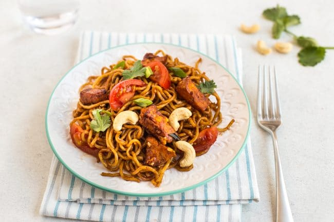 Spicy sweet potato noodles with tomatoes and cashew nuts, on a plate with a striped napkin
