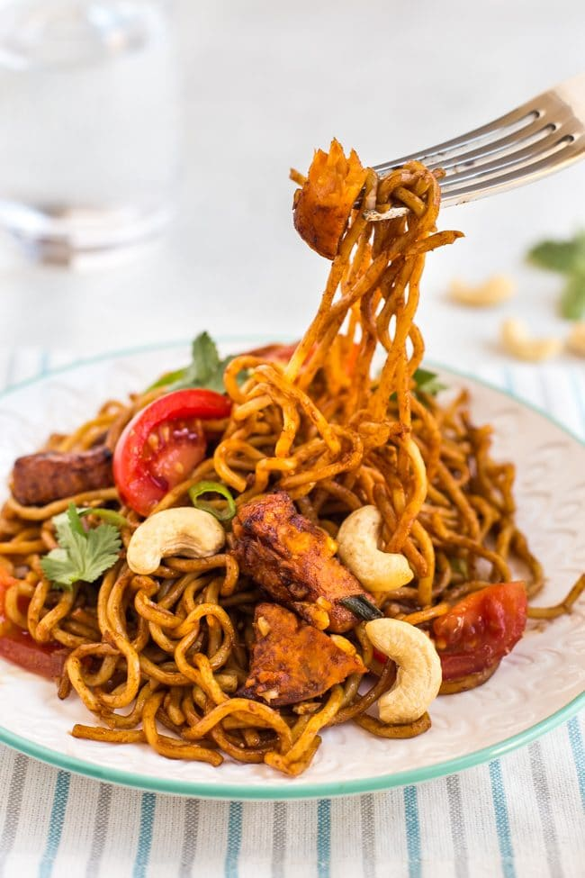 Spicy sweet potato noodles with a fork taking a scoop