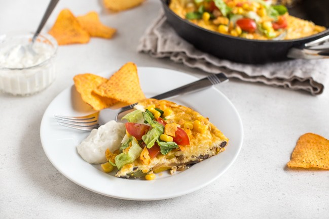 Slice of taco frittata with toppings on a plate with tortilla chips and sour cream