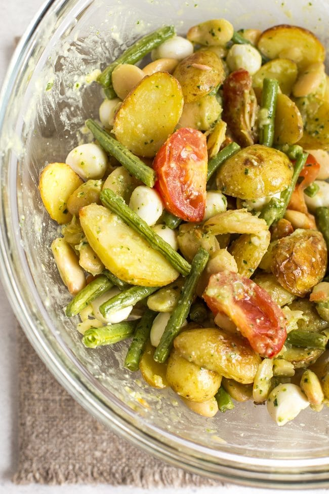 Bean and potato salad in a bowl being mixed with pesto dressing