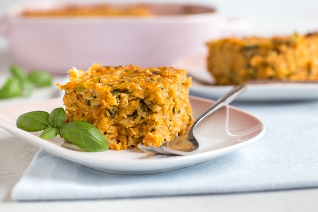 Landscape photo of a very veggie oat bar on a plate with fresh basil and a fork