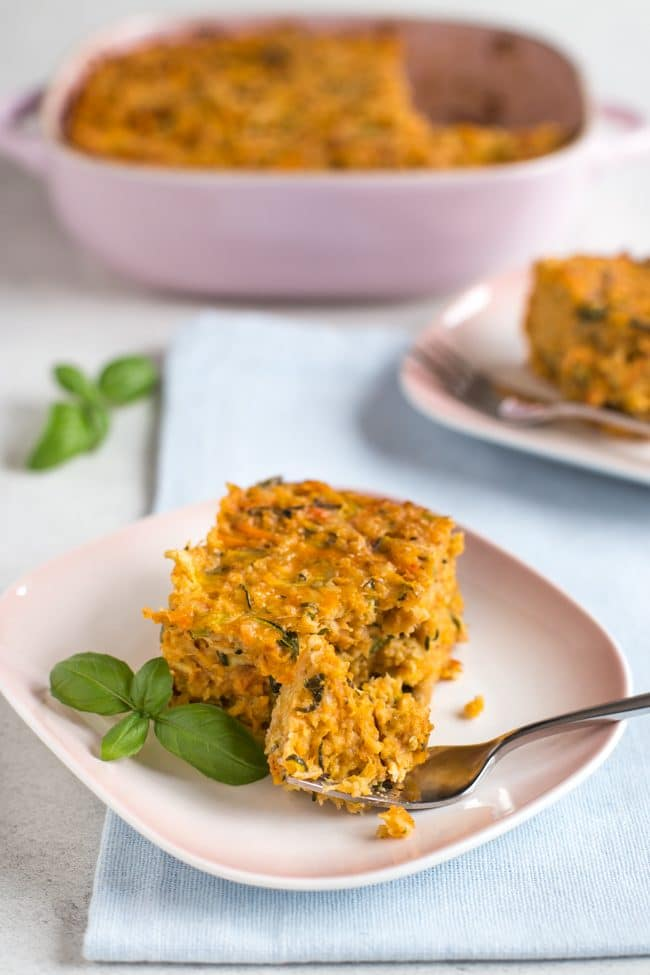 Very veggie oat bar on a place with fresh parsley and a fork taking a bite