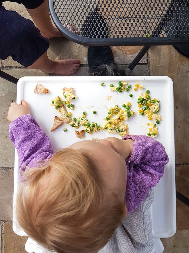 Baby eating food at a highchair, shot from above