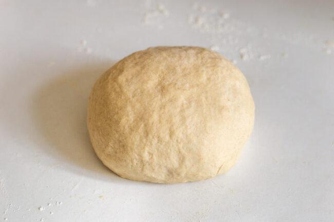 A smooth ball of bread dough on a worktop.