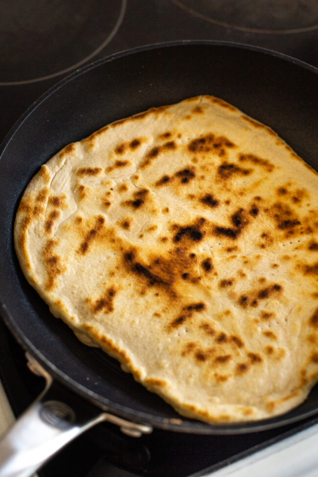 A crispy homemade flatbread cooking in a frying pan.