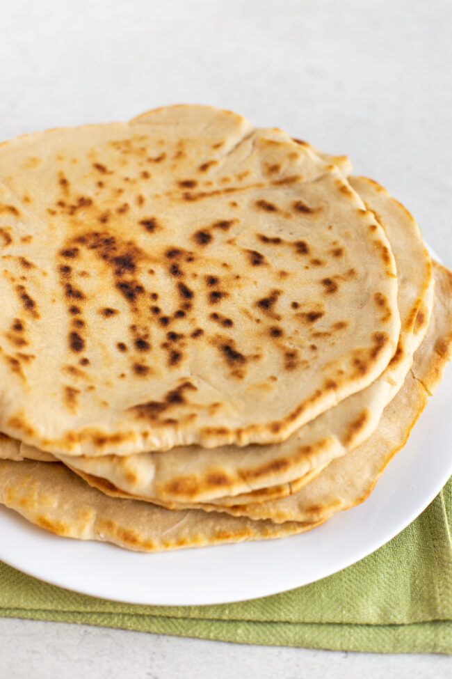 A stack of homemade flatbreads on a plate.