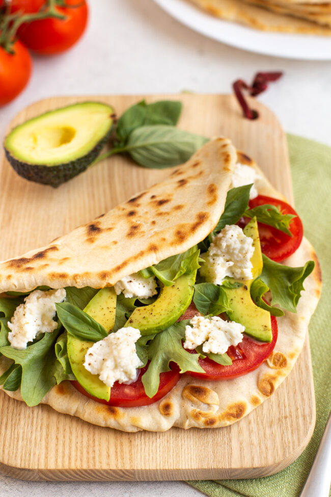 A homemade piadina flatbread stuffed with tomatoes and mozzarella cheese.