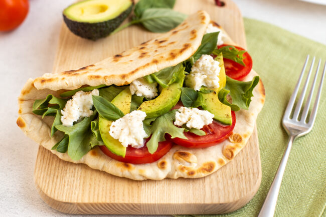 A homemade flatbread on a board, stuffed with tomatoes, avocado and mozzarella cheese.
