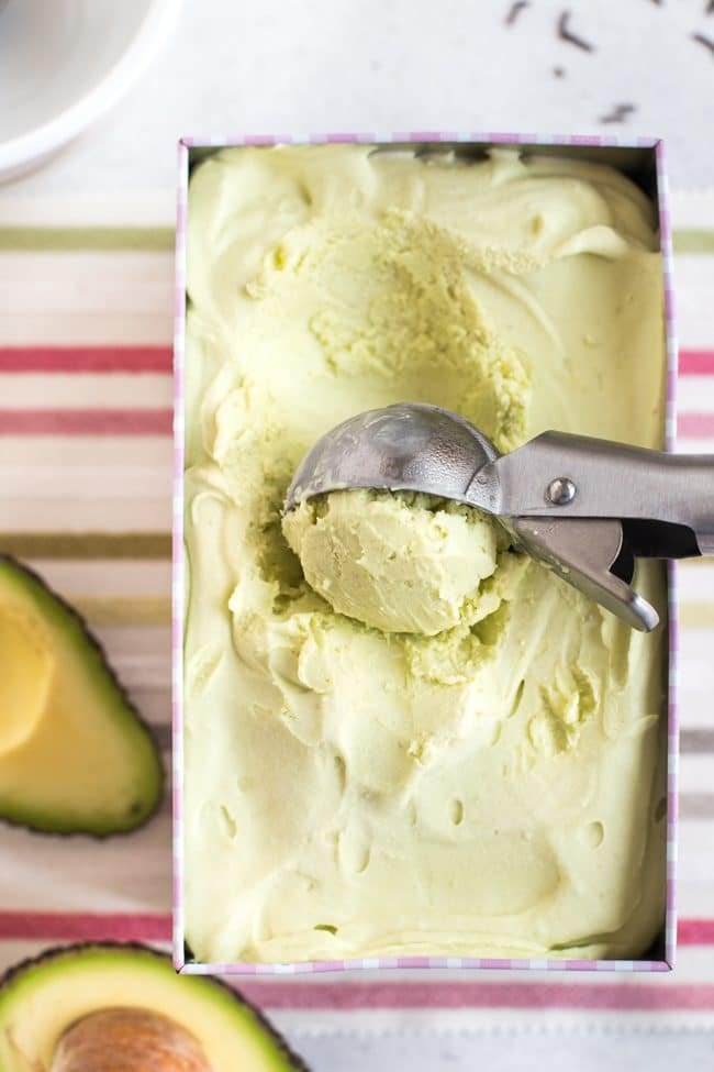 Avocado ice cream in a tub with a scoop being taken