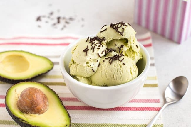 Avocado ice cream in a white bowl with chocolate sprinkles