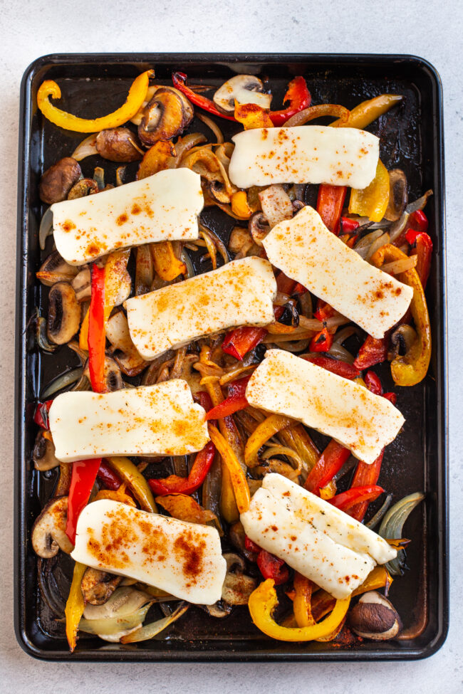 Roasted vegetables on a baking tray, topped with sliced halloumi cheese.