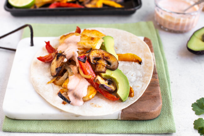 A small flour tortilla topped with roasted vegetables, halloumi cheese and avocado.