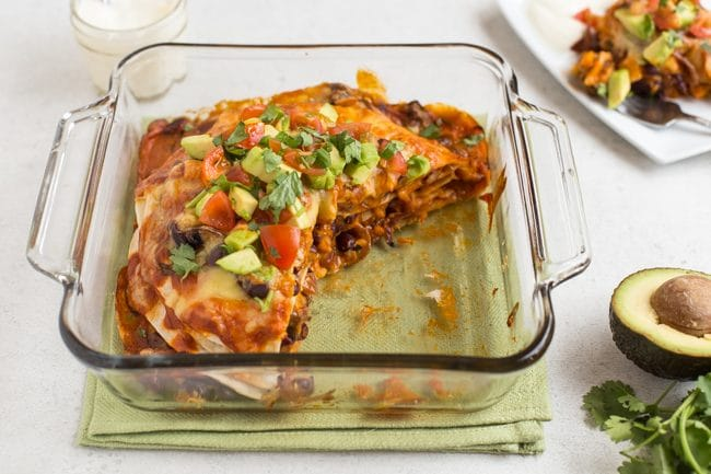 Veggie enchilada stack in a baking dish with a large slice removed