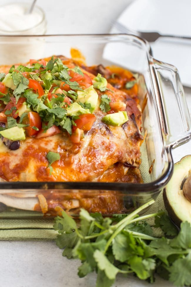 Veggie enchilada stack in a baking dish, topped with avocado and tomatoes