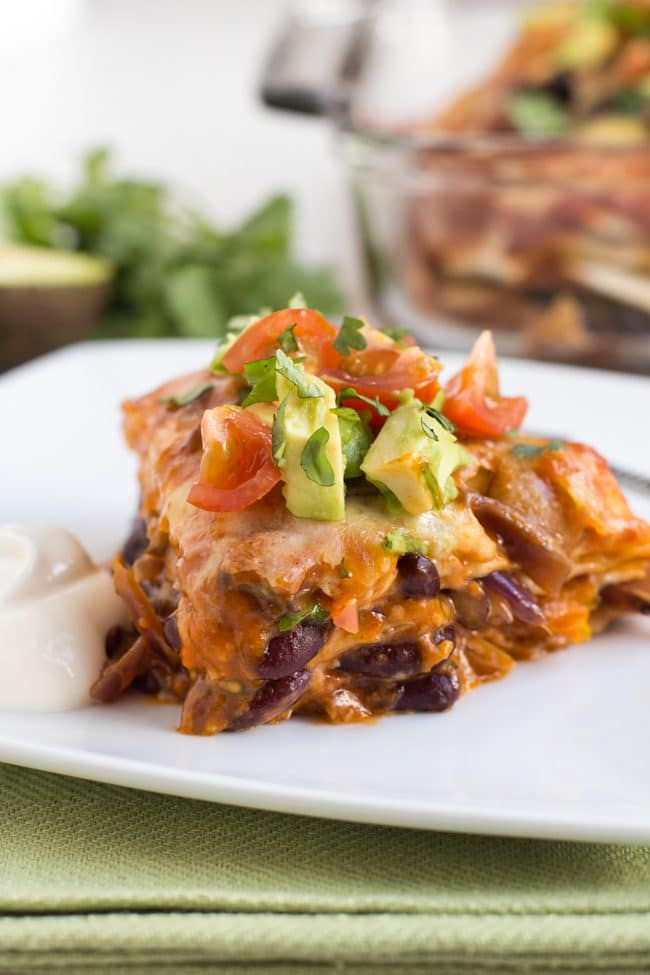 Portion of veggie enchilada stack on a plate topped with avocado and tomatoes
