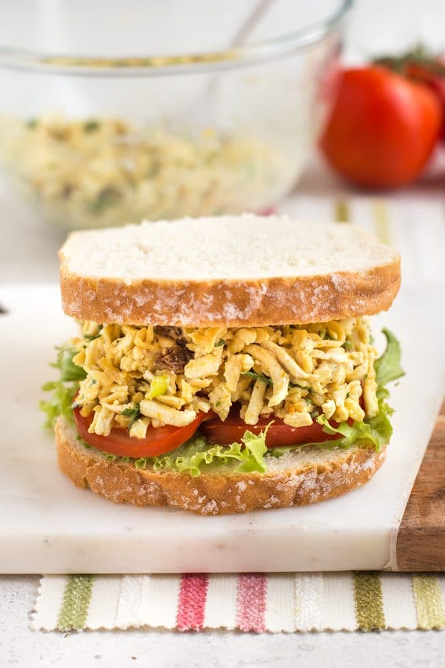 Sandwich on a board, filled with tomato slices and coronation tofu salad