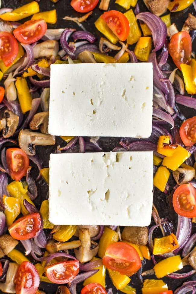 Slices of feta cheese on top of part-roasted Mediterranean vegetables