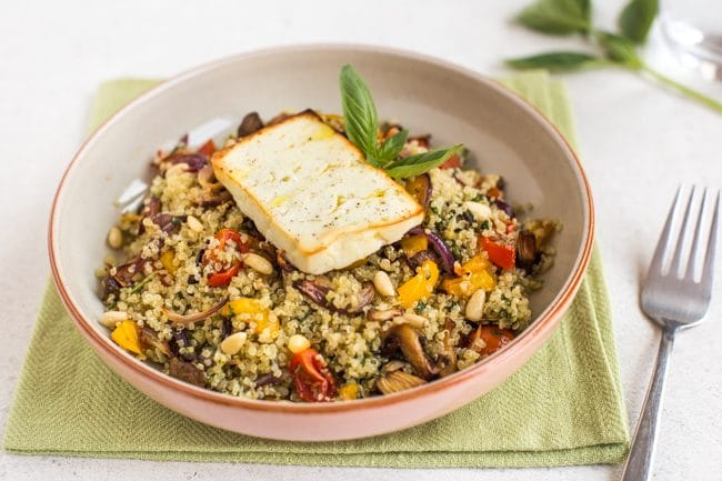 Vegetable quinoa in a bowl topped with a piece of roasted feta, on a green napkin