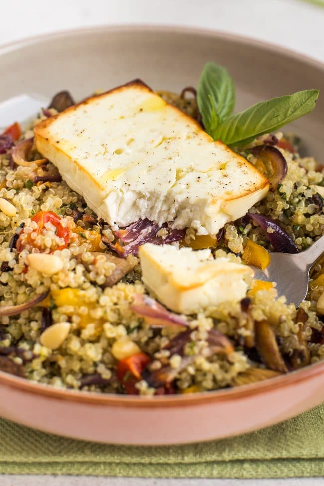 Slice of roasted feta with a scoop removed, on top of roasted vegetable quinoa