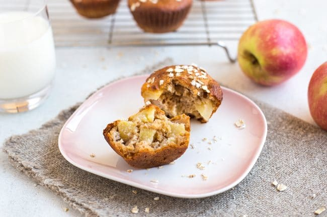 Apple and cinnamon breakfast muffin torn in half on a pink plate