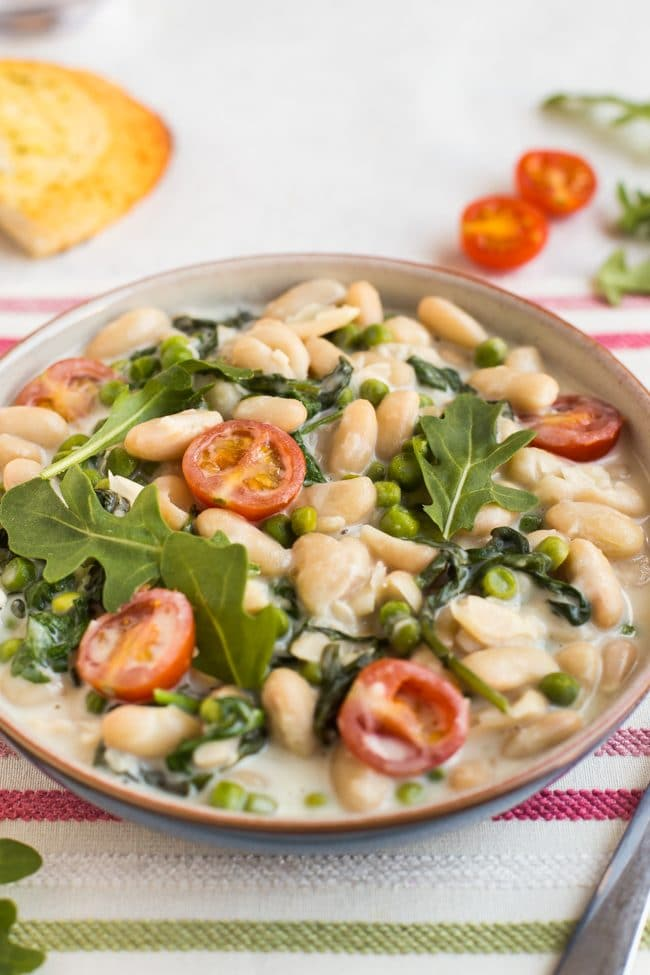 Creamy white beans with tomatoes and rocket in a bowl
