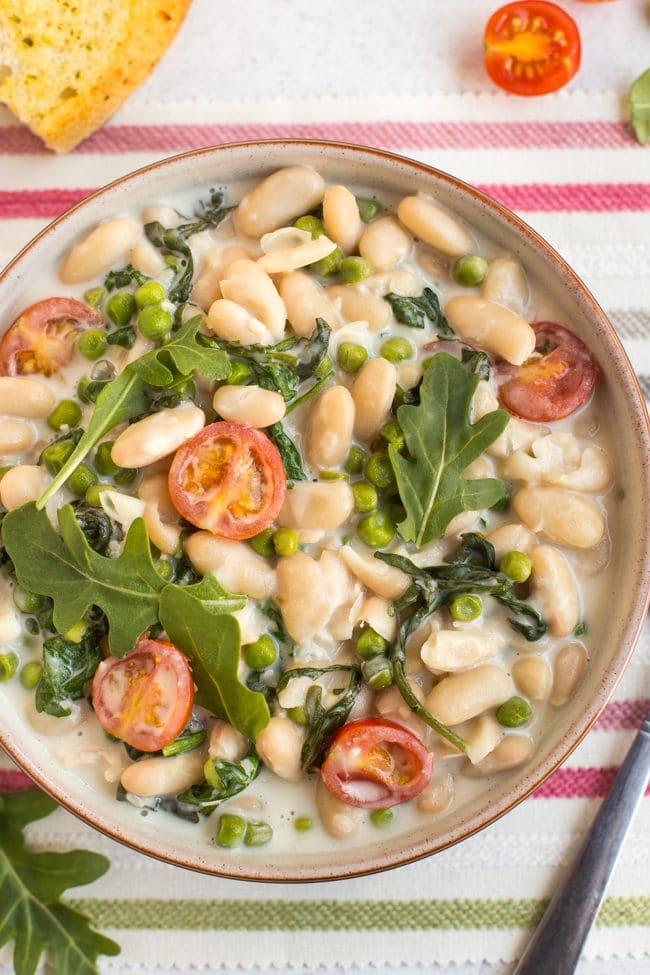Close up of creamy white beans with tomatoes and rocket in a bowl