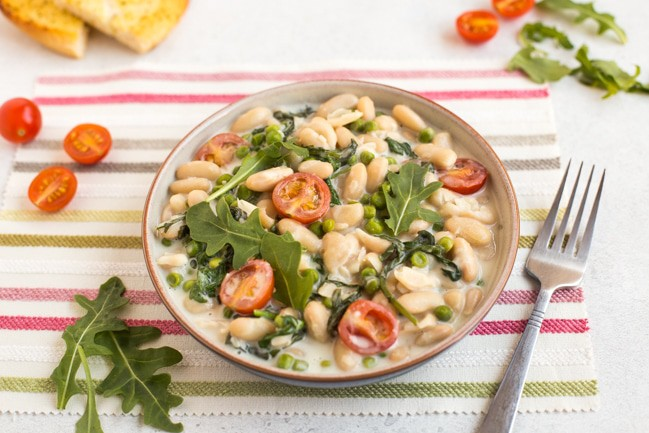 Creamy white beans with rocket and tomatoes in a bowl with a fork