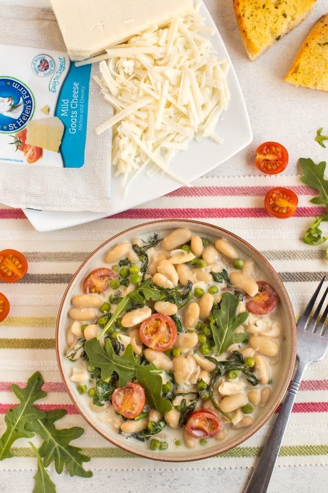 Creamy white beans with rocket and tomatoes in a bowl with a plate of grated goat's cheese