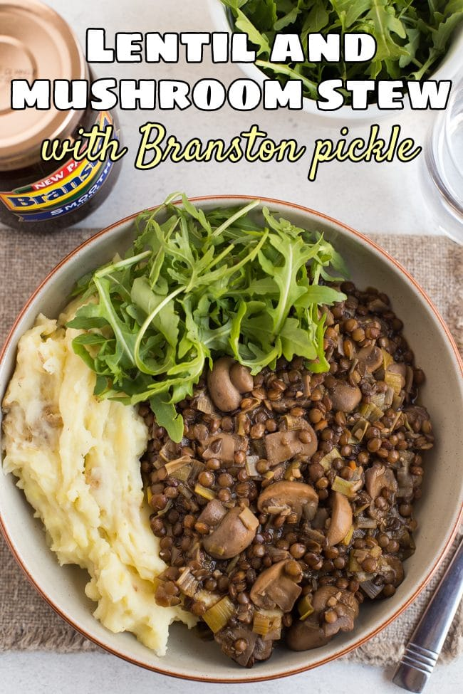 Portion of lentil and mushroom stew in a bowl with cheesy mashed potato and rocket