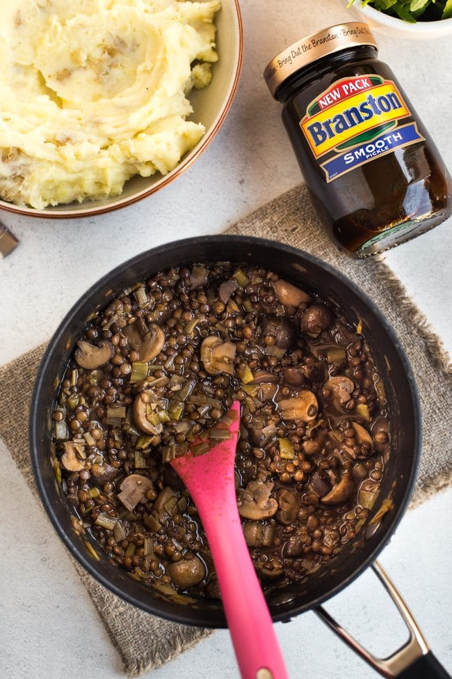 Lentil and mushroom stew in a saucepan with a jar of Branston pickle