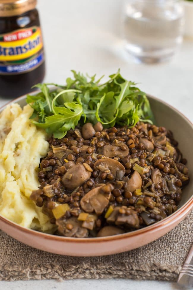 Lentil and mushroom stew in a bowl with cheesy mashed potato and rocket