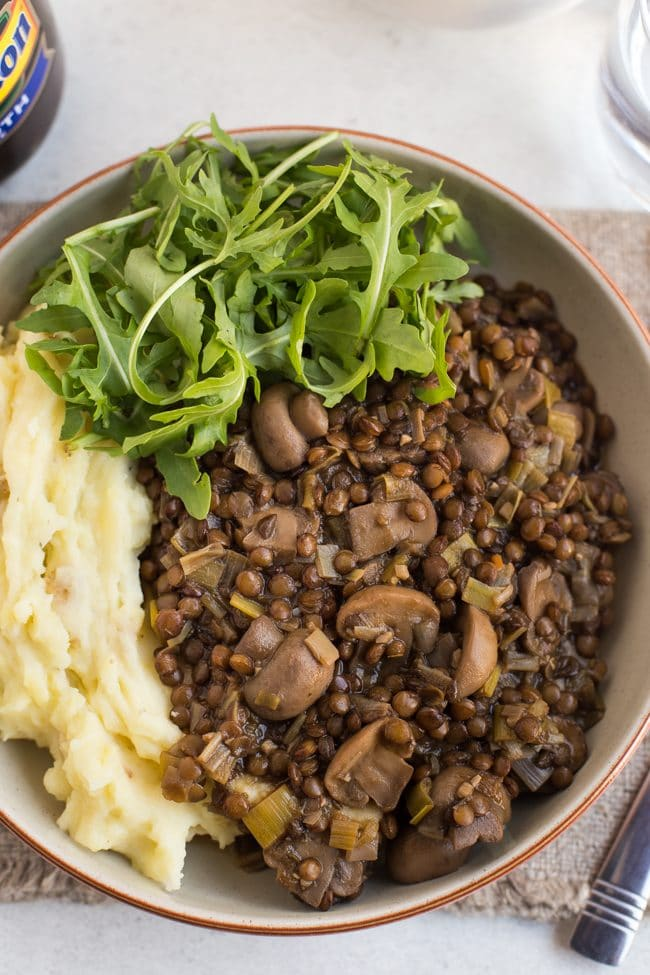 Lentil and mushroom stew in bowl with cheesy mashed potato and rocket