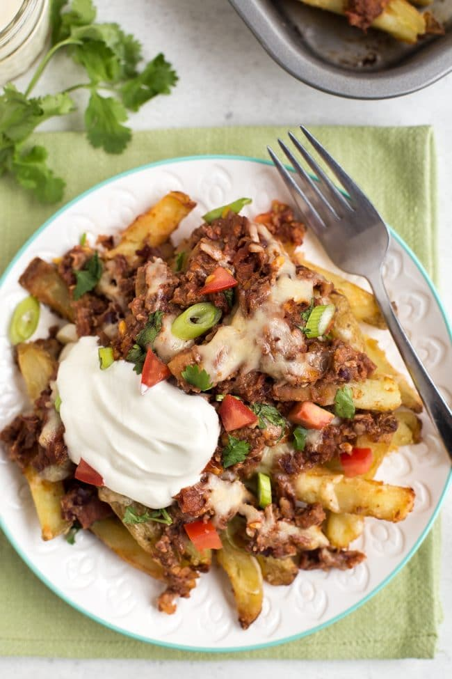 Portion of vegetarian chilli cheese fries on a plate, topped with sour cream