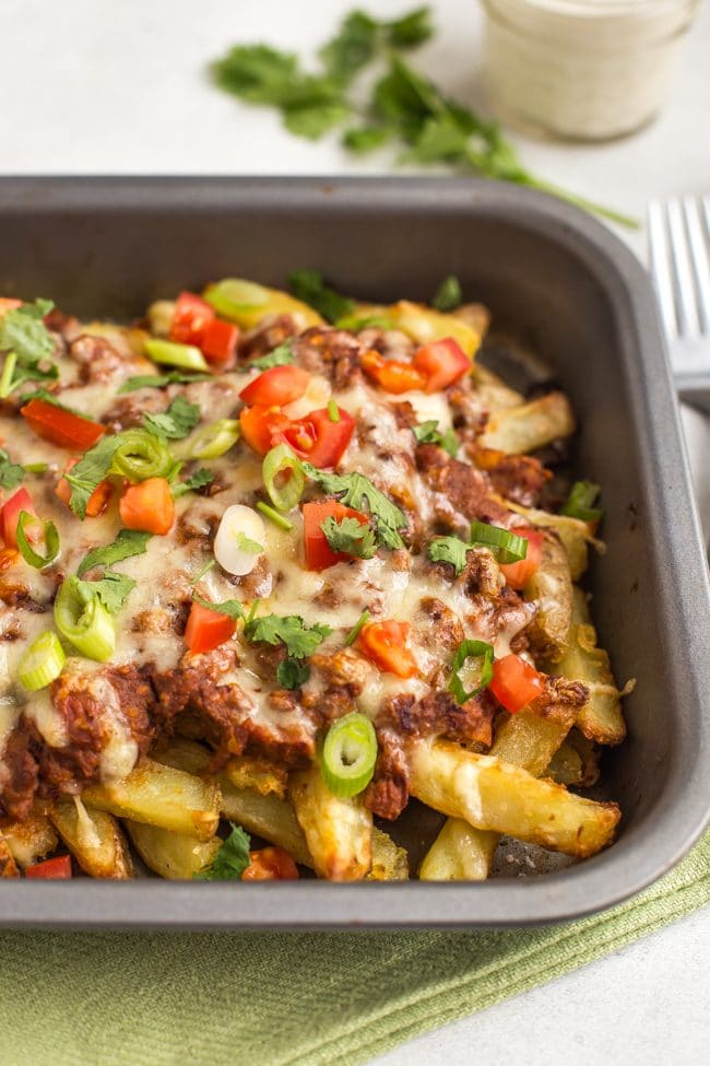 Vegetarian chilli cheese fries in a baking tray, topped with tomatoes and spring onions