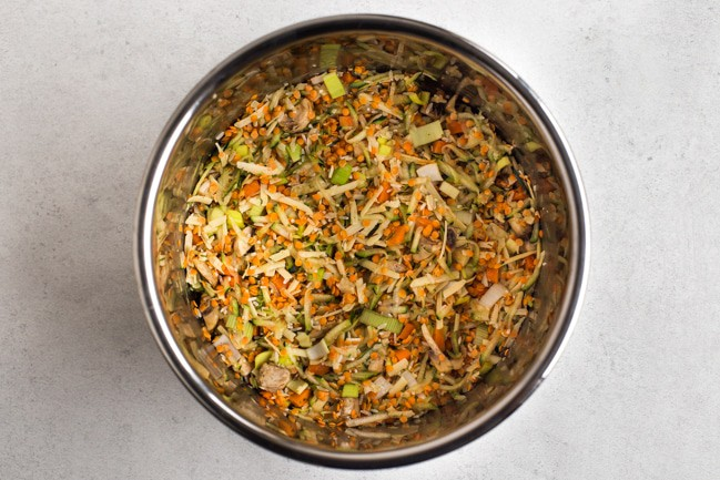 Uncooked lentils, rice and vegetables in the Instant Pot bowl