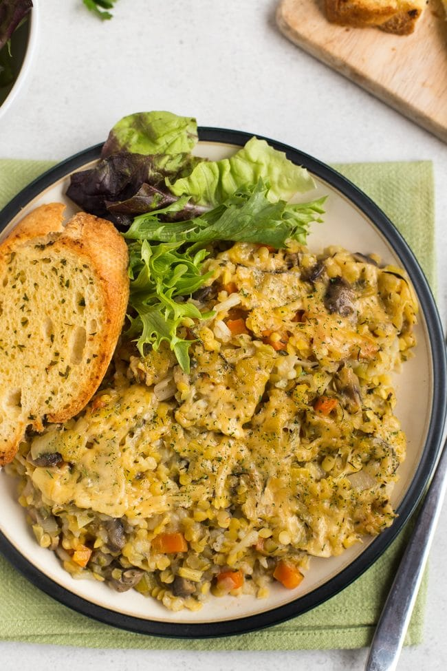 Portion of Instant Pot very veggie lentil bake on a plate with garlic bread and salad