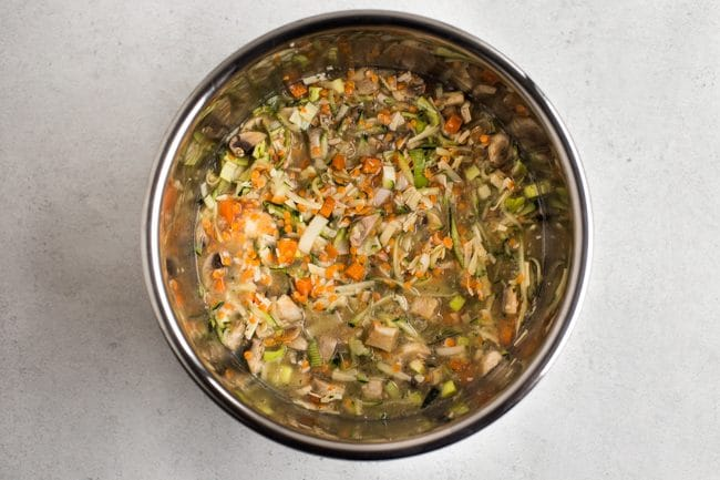 Uncooked lentils, rice and vegetables in vegetable stock in the Instant Pot bowl