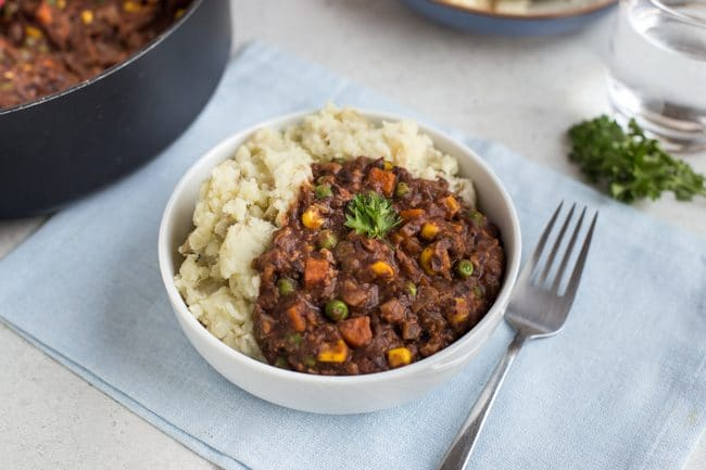 Portion of vegetarian savoury mince in a bowl with mashed potato