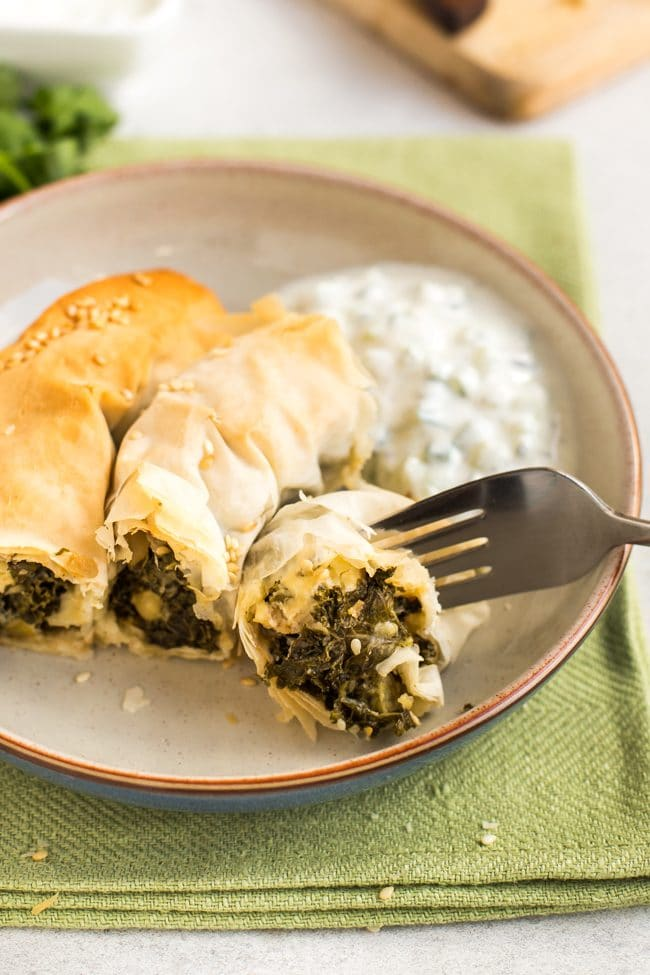 Slice of kale spanakopita spiral on a plate with homemade tzatziki