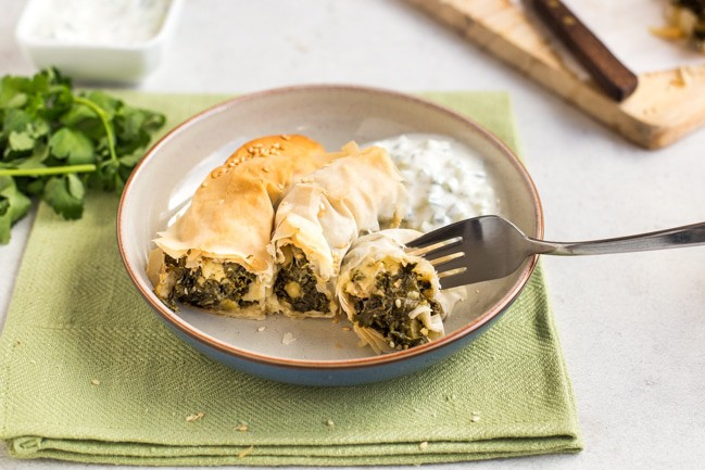 Slice of kale spanakopita spiral on a plate with a fork taking a piece