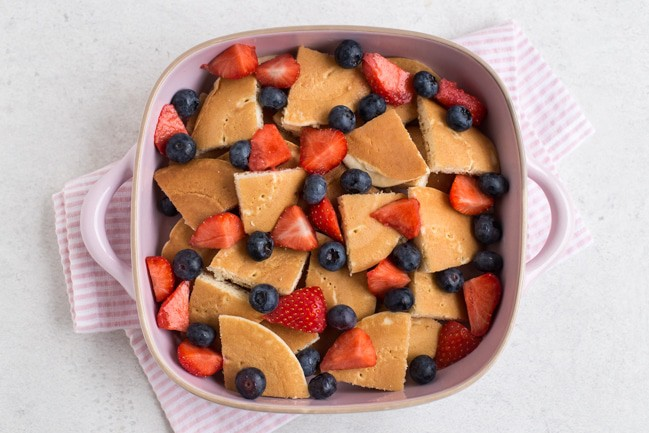 Pancakes and fresh berries in a baking dish