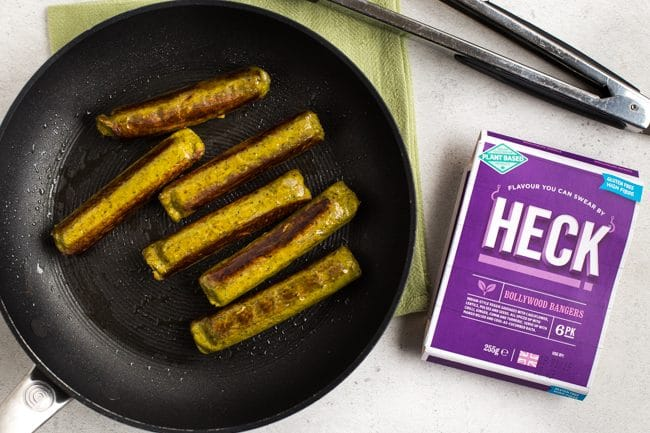 Heck Bollywood Bangers vegan sausages cooked in a frying pan