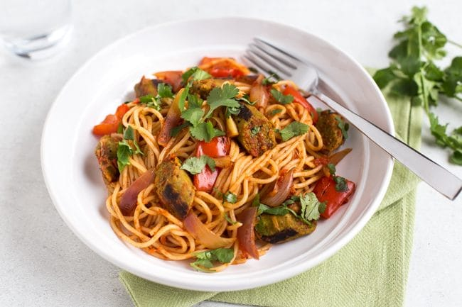 Portion of vegan curried sausage pasta in a bowl topped with cilantro