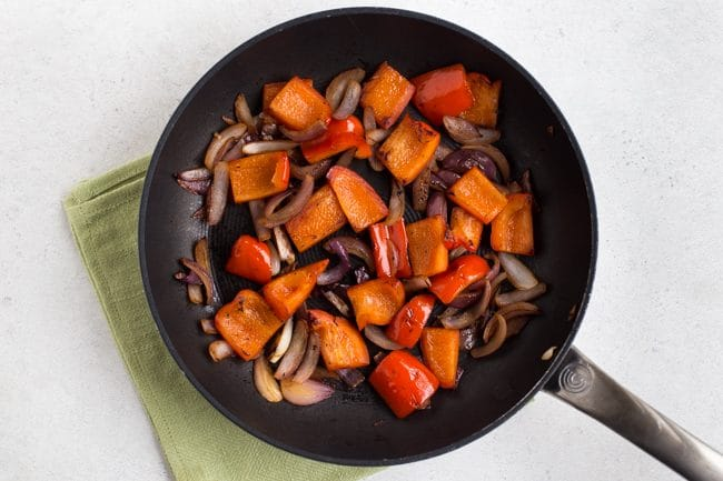 Peppers and onions cooked in a frying pan on a green napkin