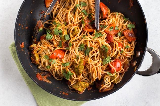 Vegan curried sausage pasta in a large wok