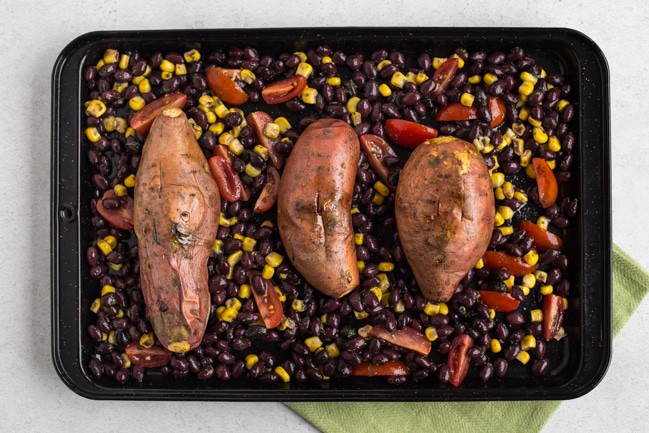 Roasted sweet potatoes on a baking tray with black beans, sweetcorn and tomatoes