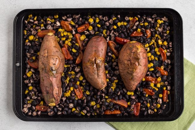 Roasted sweet potatoes on a baking tray with roasted black beans, sweetcorn and roasted tomatoes