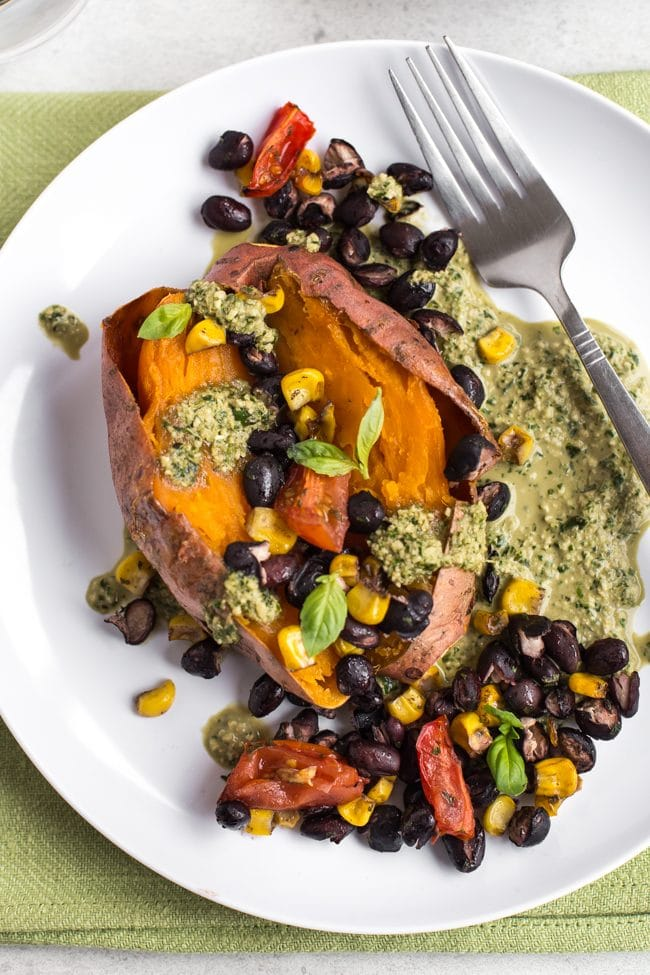 A vegan loaded sweet potato shot from above, with roasted black beans and homemade vegan pesto
