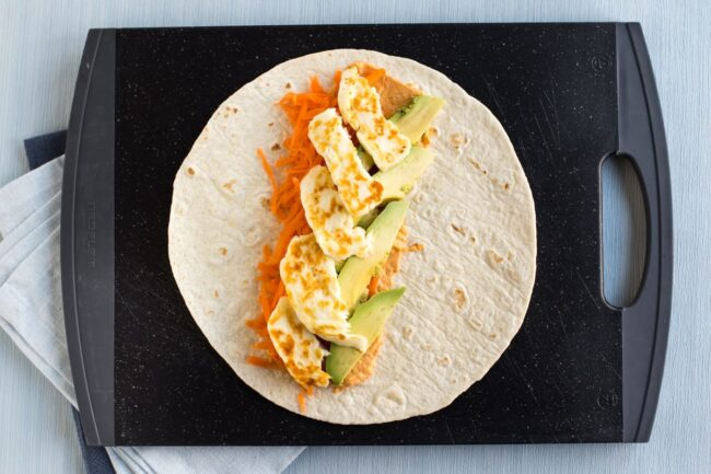 Large flour tortilla topped with grated carrot, fried halloumi and avocado slices
